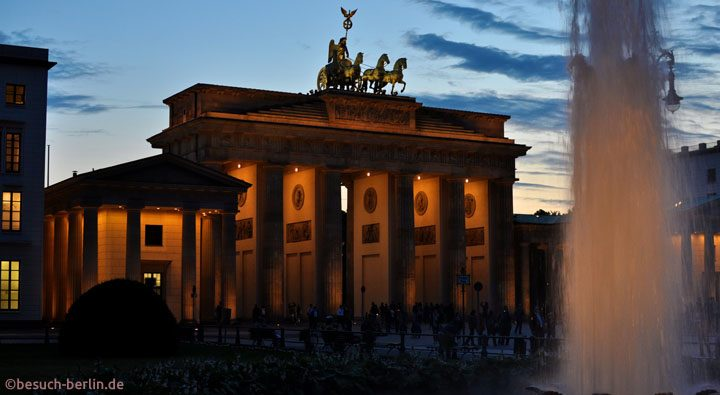 Brandenburger Tor in Berlin mit Brunnen in Abendstimmung